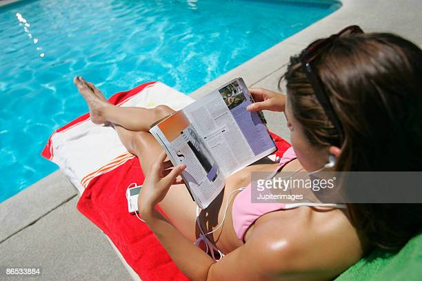 Woman reading magazine beside pool
