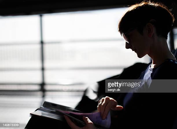 Femme lisant un magazine de l'aéroport