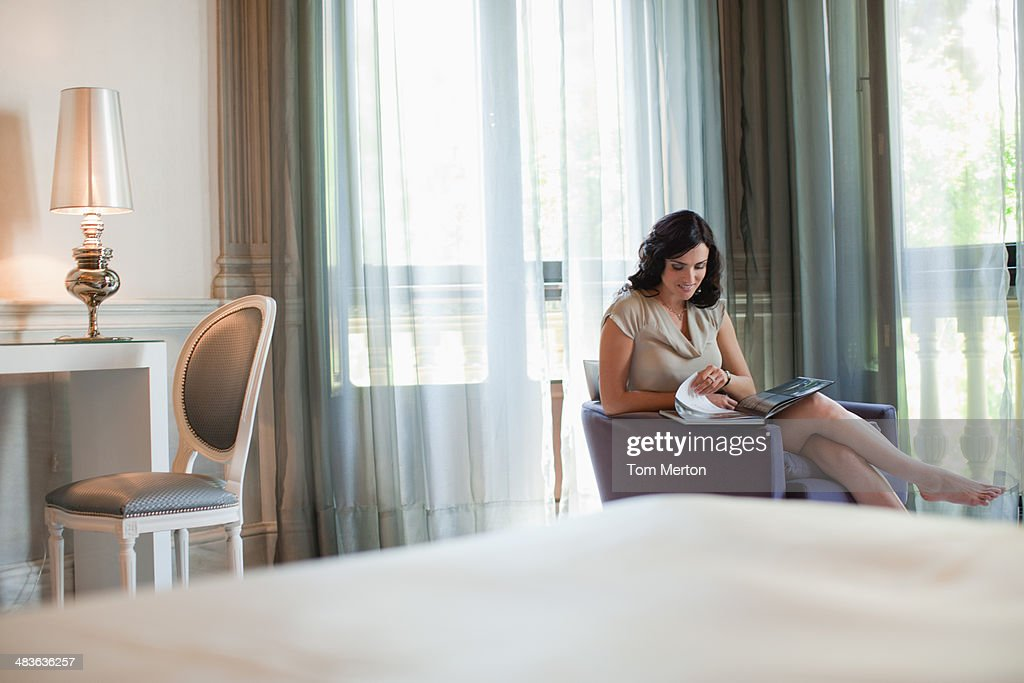 Woman reading magazine in hotel room : Stock Photo