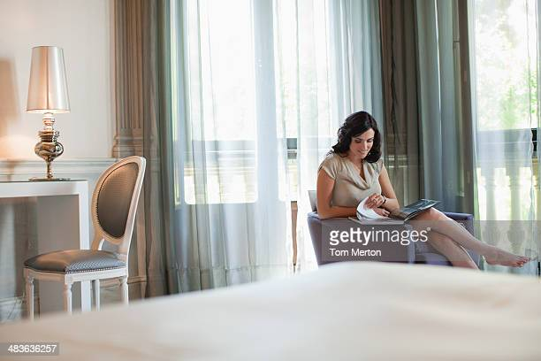Woman reading magazine in hotel room