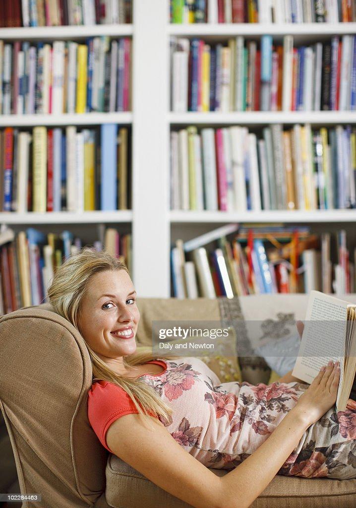 Woman reading magazine on sofa : Stock Photo