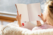 Woman reading magazine with empty white blank pages. Mockup and template for your own content. Photo from behind.