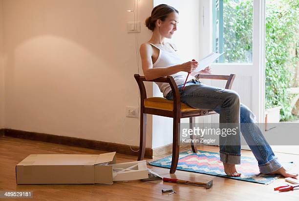 woman reading manual, holding screwdriver
