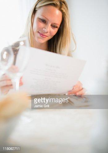 Woman reading menu at restaurant : Stock Photo