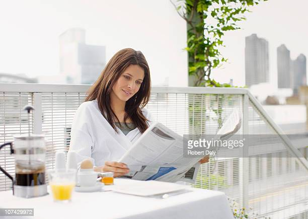 Woman reading newspaper and having breakfast on balcony
