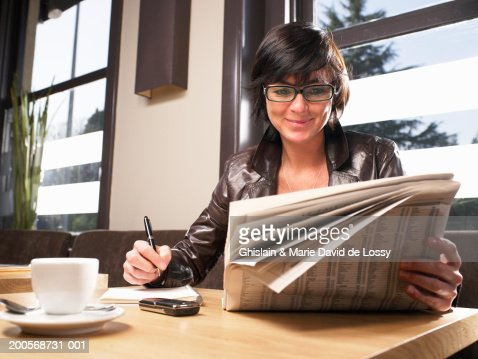 Woman reading newspaper at restaurant : Stock Photo