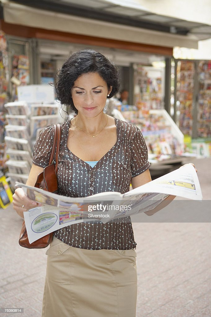 Woman reading newspaper in street : Stock Photo