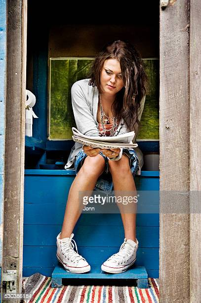 Woman reading newspaper inside outhouse