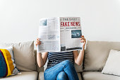 Woman reading newspaper on a couch  ***These are our own 3D generic designs. They do not infringe on any copyrighted designs.***