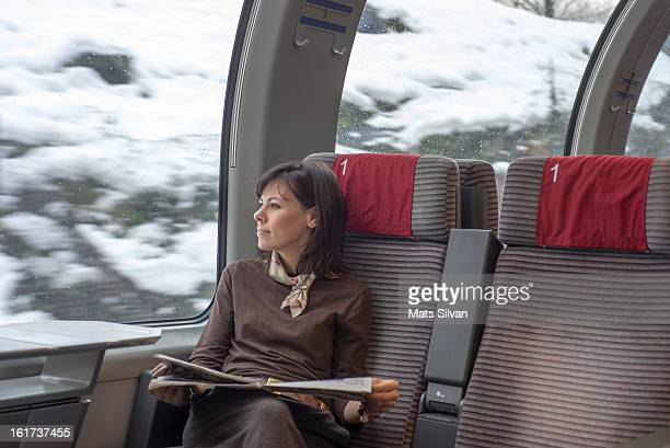 Woman reading newspaper on a train