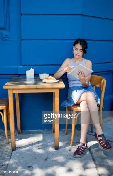 女性のカフェでタブレット コンピューターで読む
