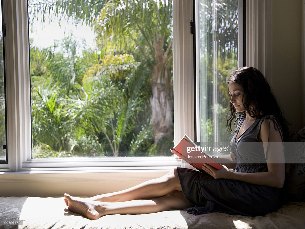 woman reading on a window bench : Stock Photo