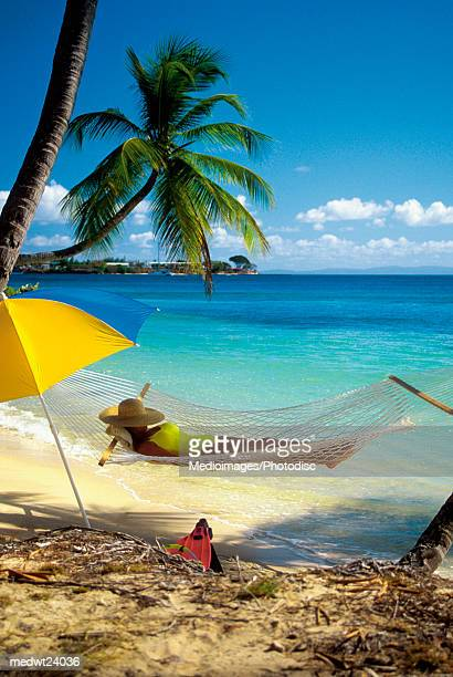 Woman reading on hammock on Pigeon Point Beach on Tobago, Caribbean