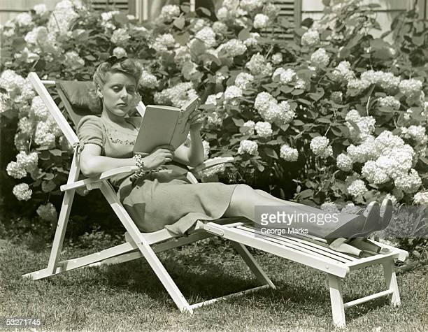 Woman reading on lounge chair outdoors