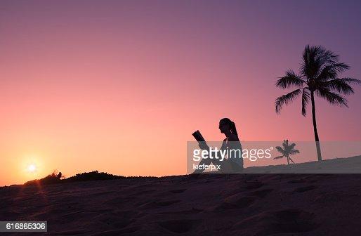 Woman reading on the beach : Stock Photo