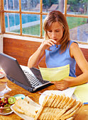 Woman reading paperwork and working on a laptop computer