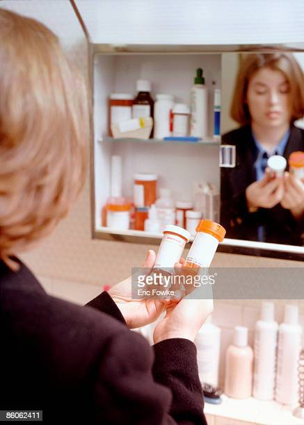 Woman reading prescription medication in bathroom