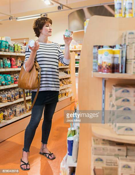 woman reading product label in supermarket