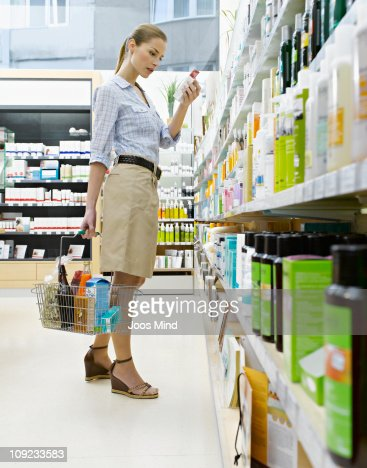 woman reading product packaging, holding basket : Stock Photo
