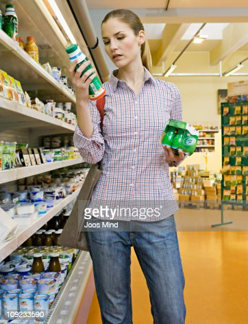 woman reading product packaging in supermarket : Foto stock