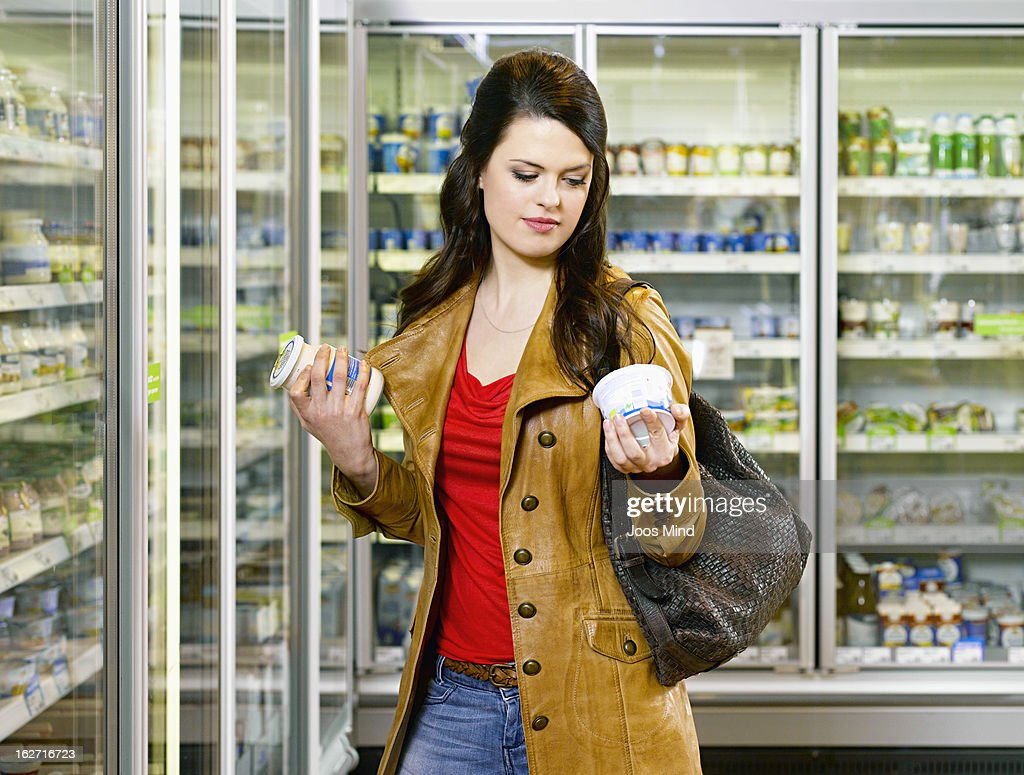 woman reading product packaging in supermarket : Stock Photo