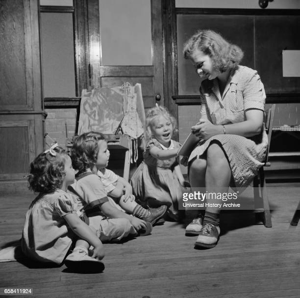 Woman Reading Story to Three Young Children at Child Care Center New Britain Connecticut USA Gordon Parks for Office of War Information June 1943