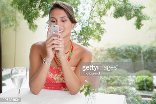 Woman reading text message at dining table