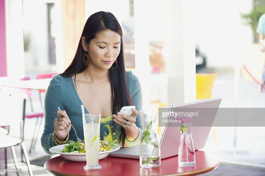 Woman reading text message while eating food in a restaurant : Stock Photo