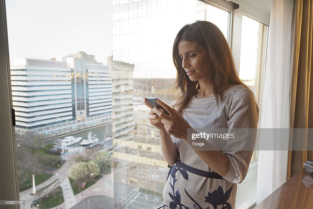 Woman reading text on phone with cityscape : Stock Photo