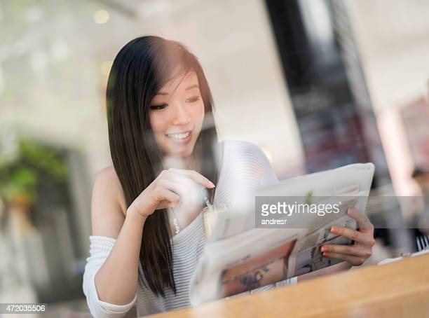 Woman reading the newspaper at a cafe