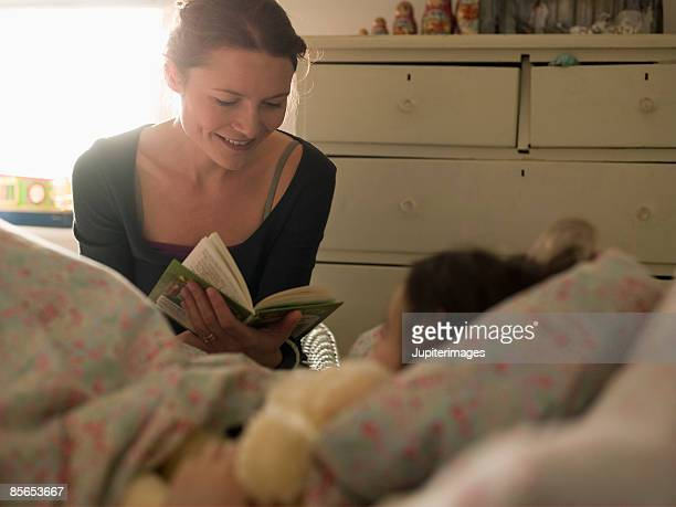 Woman reading to daughter in bed