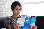 Young hispanic woman laying on couch at home, holding a travel flyer and planning next trip. Copy space on window.