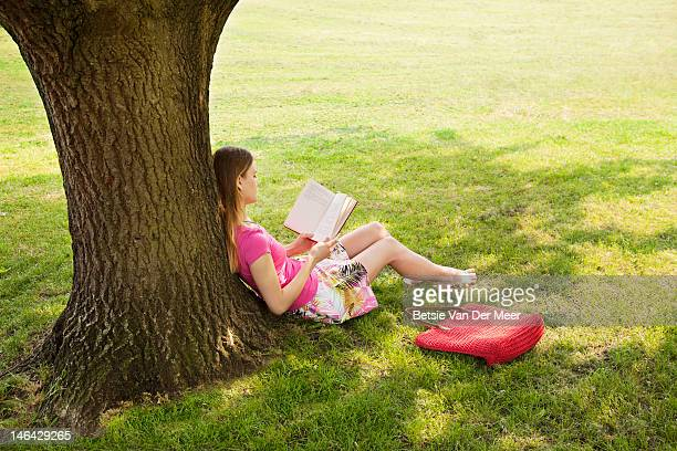 woman reading under tree in park.
