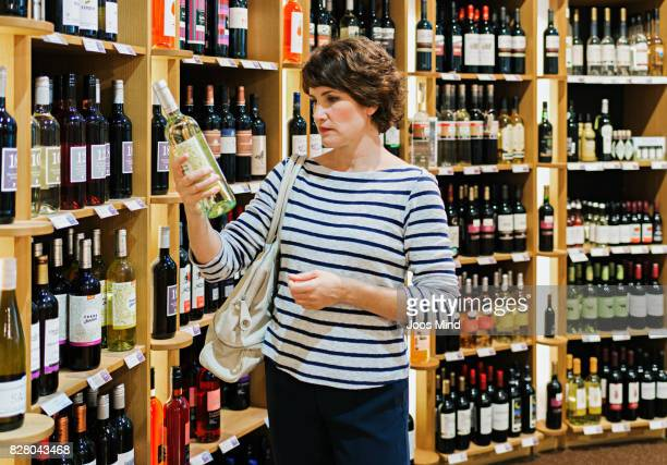 woman reading wine bottle label in supermarket