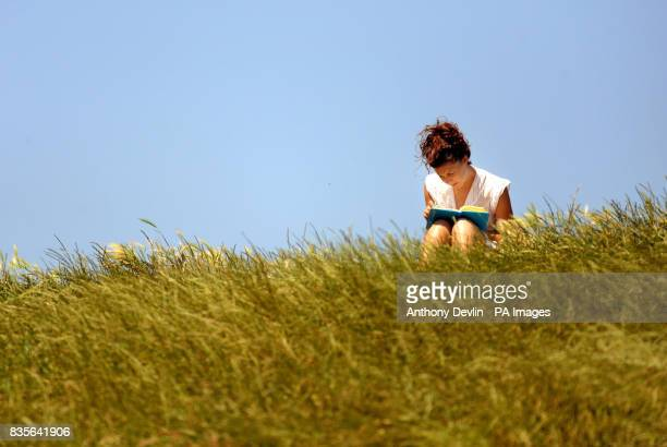 A woman reads a book as people enjoy the sunshine on Primrose Hill London