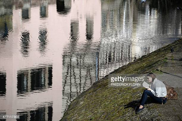 A woman reads a book as she enjoys unusually high seasonal temperatures in Strasbourg eastern France on March 7 2014 AFP PHOTO / FREDERICK FLORIN