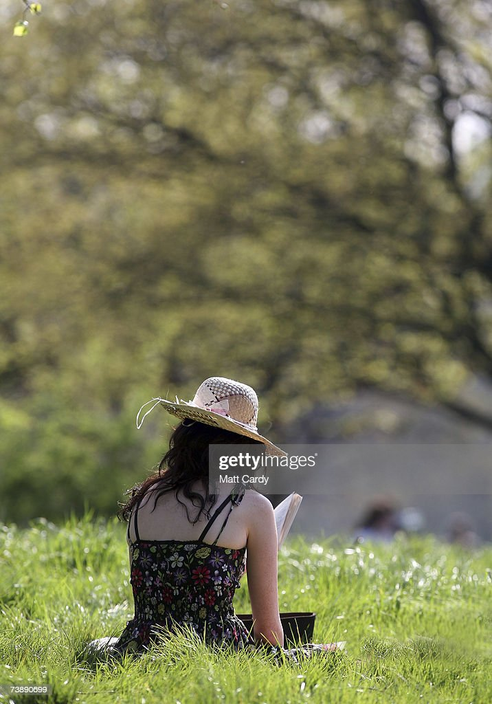 A woman reads a book as she sits in the shade as she enjoys the hot weather in Primrose Hill on April 15, 2007 in London. The un-seasonably warm weather has heralded the start to what weather forecasters predict will be a record breaking summer.