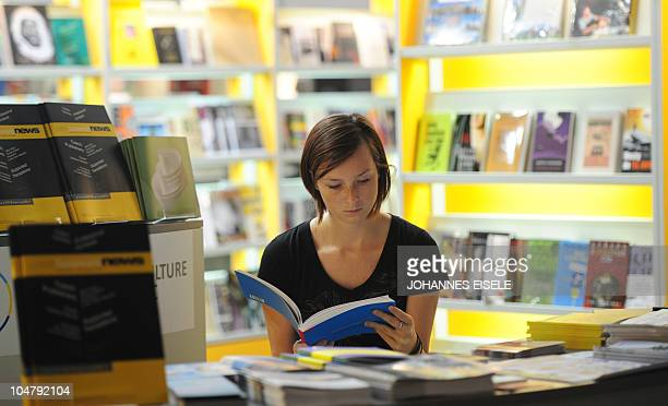 A woman reads a book at a stand before the start of the 62nd Frankfurt Book Fair in Frankfurt am Main on October 5 where Argentina is this year's...