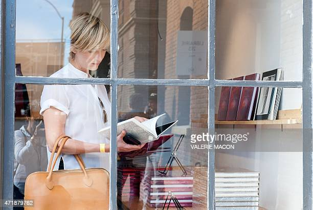A woman reads a book at the Paris Photo Exhibit in Los Angeles California on May 1 2015 The Paris Photos is held till May 3rd at the Paramount Studio...