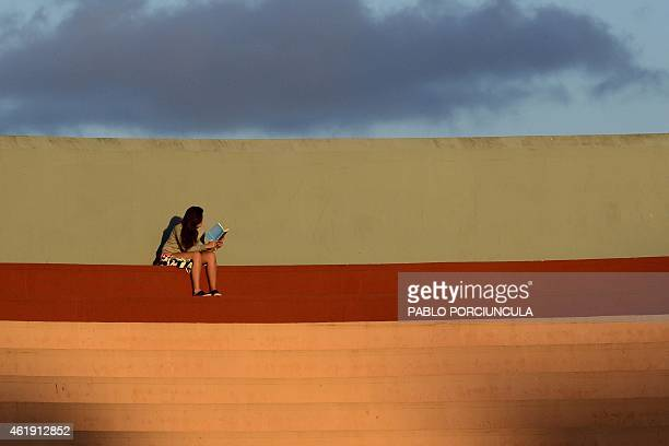 A woman reads a book during the South American U20 football match beetwen Colombia and Venezuela at Domingo Burgueno stadium in Maldonado 130 km east...