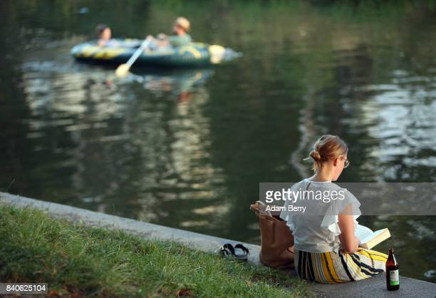A woman reads a book during warm evening weather in the Kreuzberg district on August 29 2017 in Berlin Germany Berliners and tourists experienced a...