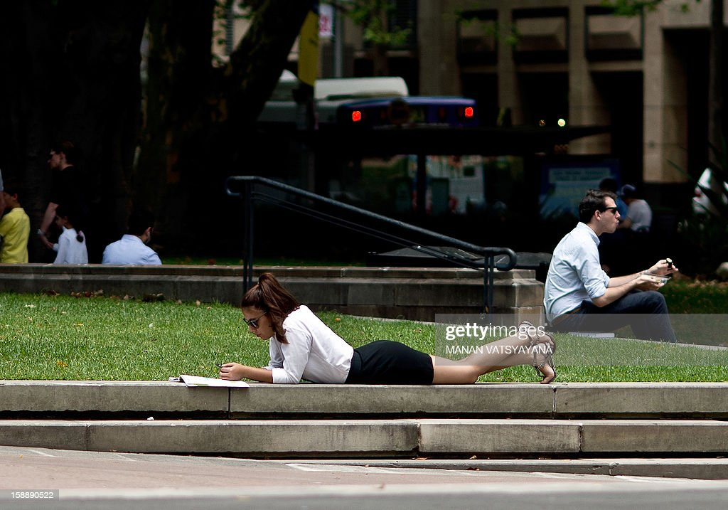 A woman reads a book in Sydney's Hyde Park on January 3, 2013. Sydney's ranking has consistently been placed in the top ten liveable cities in the world, scoring well for having low pollution levels and abundant green spaces.