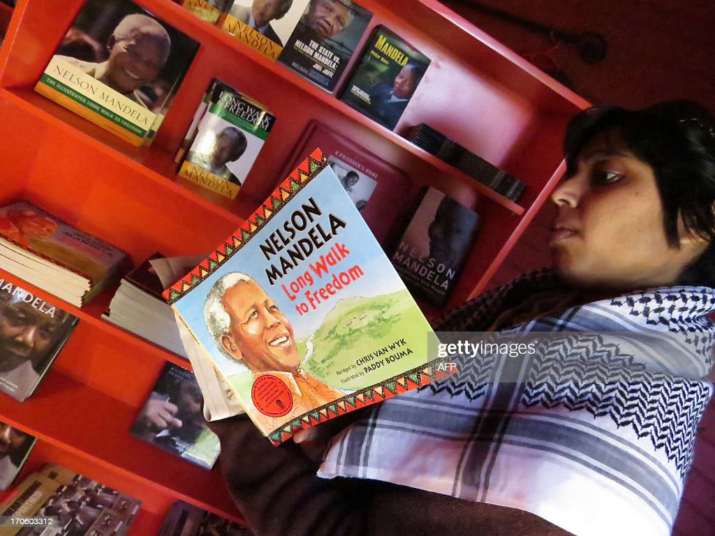 A woman reads a book in the bookstore at the Apartheid Museum near the 'capture site' of former South African President Nelson Mandela in Howick, approximately 150 kilometers west of Durban, in the KwaZulu Natal midlands. Nelson Mandela was admitted to a Pretoria hospital on June 8, 2013, because of a recurring lung infection. Nelson Mandela seems to be on the road to recovery from a recurrent lung infection, a grandson said today after visiting the anti-apartheid hero in hospital. AFP PHOTO / Anesh Debiky