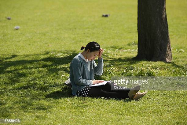 A woman reads a book in the sunshine in St James's Park on May 1 2013 in London England Following an unseasonally cold start to the year temperatures...
