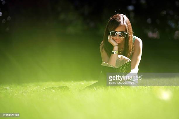 A woman reads a book in the sunshine in Victoria Tower Gardens on September 2 2011 in London England After a lengthy wet spell London was bathed in...