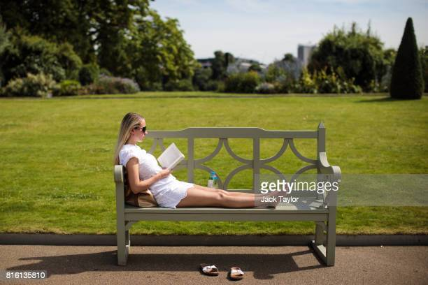 A woman reads a book on a bench in Kensington Gardens on July 17 2017 in London England Much of Britain experienced warm and sunny weather today with...