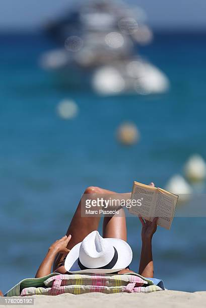 A woman reads a book on the 'Club 55' beach on August 9 2013 in SaintTropez France