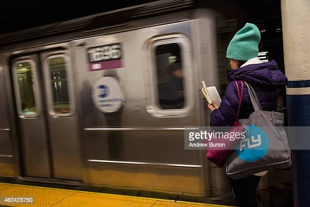 A woman reads a book waiting for an uptown 6 train at BroadwayLafeyette Station on January 28 2015 in New York City The subway returned to its normal...