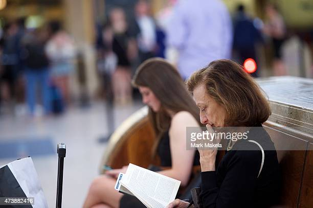 A woman reads a book while in the background travelers prepare to board their Amtrak train which resumed northbound service from 30th Street Station...