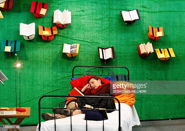A woman reads a book while lying on a bed at the Frankfurt Book Fair on October 17 2008 The world's biggest book fair is showcasing Turkey this year...
